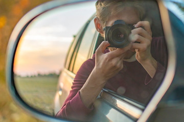 young driver taking a self portrait with professional camera in the car window  f