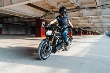 Distant plan of biker in helmet riding motorcycle at parking. Urban background.