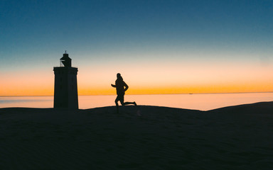 Panoramic view. Silhouette man at sunset on sand v dunách amazing at Rubjerg Knude in Denmark