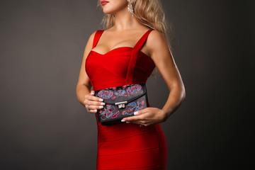 Woman in stylish red dress . Perfect female sexy girl holding handbag-dark background