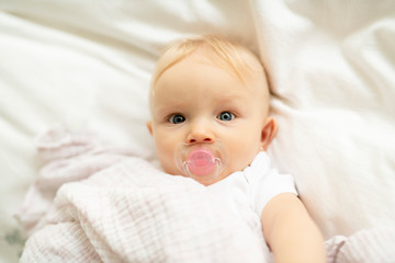 A cute baby with pacifier lying on a white bed