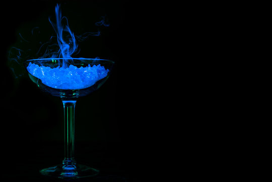 Glowing blue drink with neon smoke in martini glass