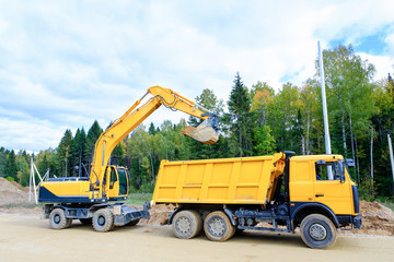The wheel excavator loads the earth with a bucket to the body of a multi-ton dump truck on the construction site
