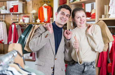 Smiling couple is satisfied of purchases and standing with package