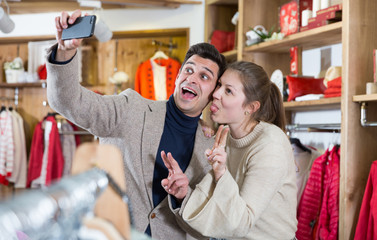 Smiling couple is satisfied of purchases and taking selfie