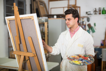 Man near easel painting on canvas