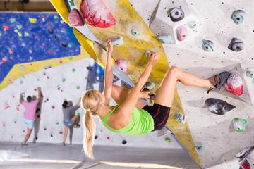 Female climbing artificial rock wall