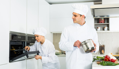 Professional chef  in uniform with pot  working with woman cook on kitchen
