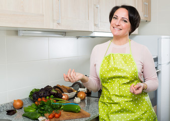 Middle age female in apron posing near kitchen top