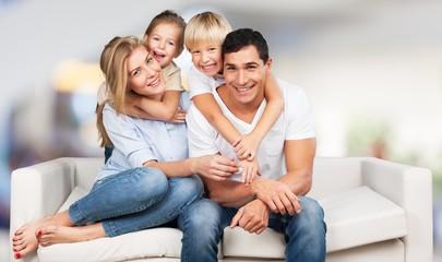 Beautiful smiling family sitting at sofa at