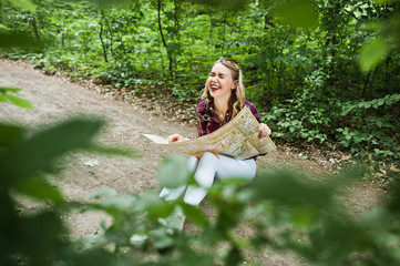 Portrait of a positive young gorgeous blonde sitting on the ground with a map in her hands in the forest.