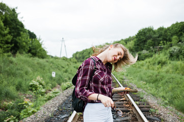 Portrait of a pretty blond girl in tartan shirt walking on the railway with map in her hands.