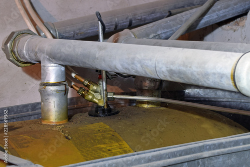 Close up of heating oil tank pipes  Overfilling has covered