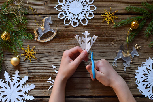 Making paper snowflakes with your own hands. Children's DIY. Merry Christmas and New Year concept. Step 2. Cut the snowflake