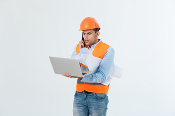 Disappointed handsome engineer wearing orange vest and jeans with helmet, isolated on white background