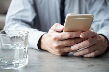 Hands of middle-aged man using application in his smartphone