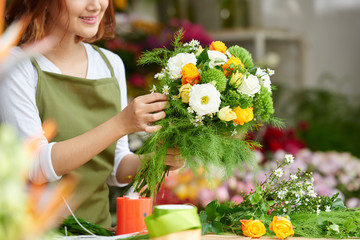 Close-up image of female florist making beautiful bouquet of fresh flowers