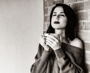 Portrait of a young caucasian woman with of coffee or tea on brick wall background . Image in black and white color