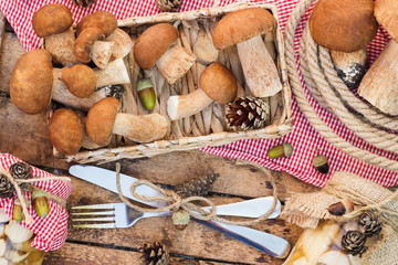 Raw white mushrooms, pine cones with dry decorations on the wooden table