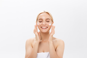 Close up beauty portrait of a laughing beautiful half naked woman applying face cream isolated over white background