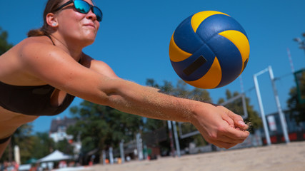 CLOSE UP: Young woman falls into the sand while striking ball with her hands.