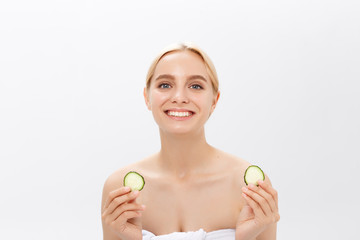 Close-up face of beautiful woman with clean fresh healthy skin and with cucumber slices. Isolated on white.