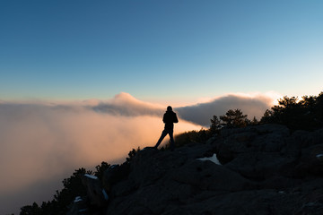 Man standing at the edge of clouds