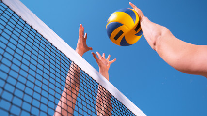 CLOSE UP: Unrecognizable young female' hands playing volleyball at the net.