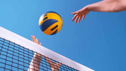 CLOSE UP Female volleyball player's hands score point by spiking ball over hands