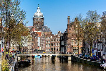 AMSTERDAM, NETHERLANDS - APRIL 11, 2018: St. Nicholas Church and Amsterdam canal with typical dutch houses. St. Nicholas Church is the city's primary Roman Catholic church.