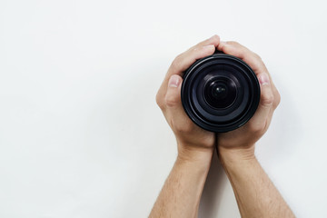 Top view of the lens held by hands. Hands are braiding the lens, top view on a light gray background. The concept of shooting, using photographic equipment. Photo courses.