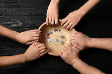 Poor people holding bowl with coins on wooden background, top view