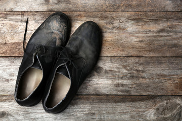 Dirty shoes and space for text on wooden background, top view. Poverty concept