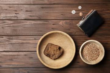 Flat lay composition with food, coins and space for text on wooden background. Poverty concept