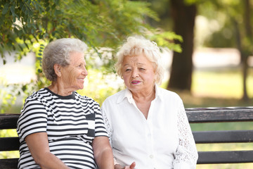 Elderly women resting on bench in park