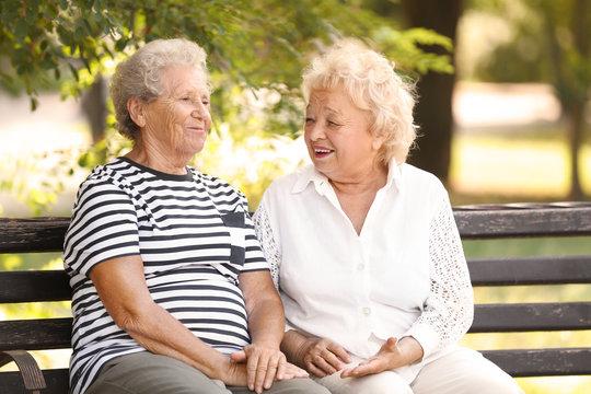 Elderly women resting on bench in park