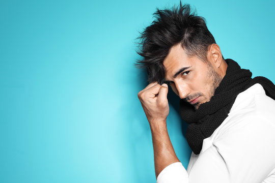 Young man with trendy hairstyle posing on color background