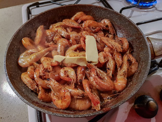 Giant orange shrimps with heads fried in oil in a frying pan on a gas stove