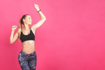 Weight loss fitness woman jumping of joy. Young sporty caucasian female model isolated on pink background.