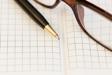 Close up Glasses and pen on notebook on table