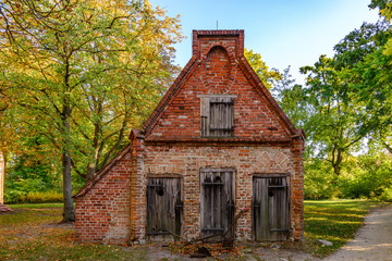Tranquil front view of small rough old brick house and wooden dirty doors and windows located in rural area in autumn with no people before sunset.