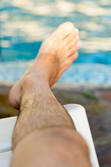 Man's feet on the background of a swimming pool.
