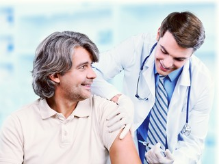 Handsome doctor making vaccination to male patient