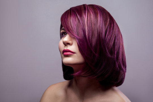 Portrait of beautiful fashion model woman with short purple colored hairstyle and makeup and looking away. indoor studio shot, isolated on gray background.