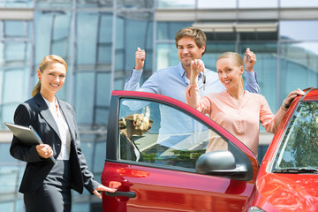 Dealer Standing Besides Couple Holding Key Of New Car