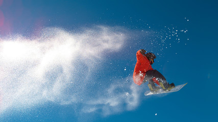 BOTTOM UP: Athletic man jumps in the air and does a cool trick on his snowboard.