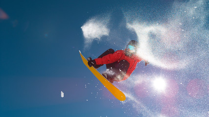 LENS FLARE: Cool view of a snowboarder doing a spinning trick high in the air.