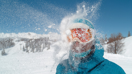 CLOSE UP: Smiling girl wearing ski goggles gets hit in the head by a snowball.