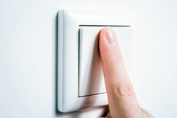 Male Finger Touching A Light Switch To Turn The Light On Or Off