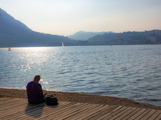 man reads book in a park sitting on the shore of the lake in Lugano, Switzerland
